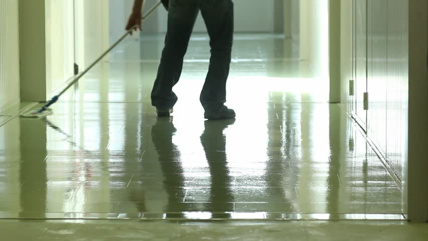A man cleaning and wipes the floor with a rag
