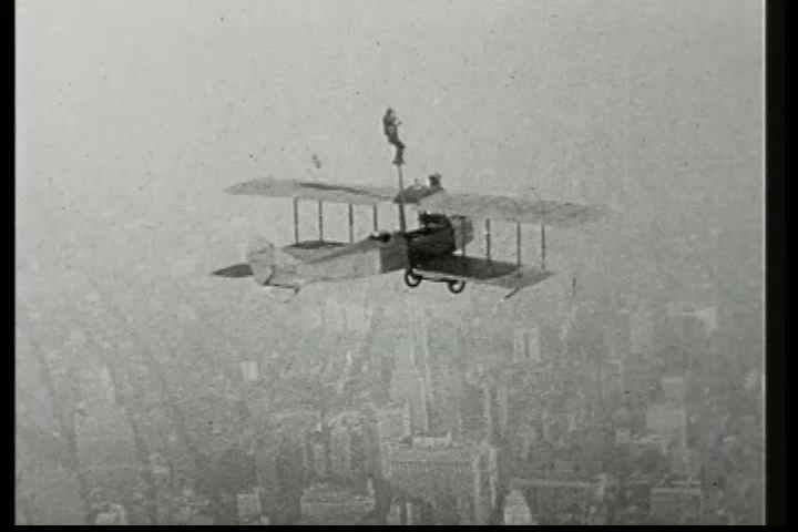 1920s - A man climbs a pole attached to a biplane in this 1928 stunt film.