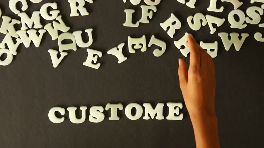 A person spelling Customers with plastic letters