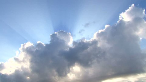 Beautiful cloudscape with large, building clouds and sunrise breaking through cloud mass.