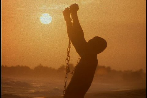 Slavery reenactment in Ghana, Africa. MS silhouette of black man in chains crouching on beach. He stands and raises his arms.