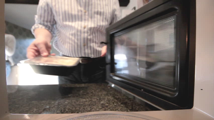 Putting ready meal in microwave