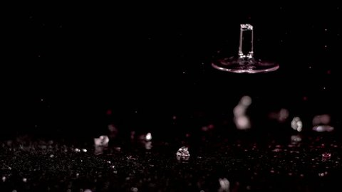 A  glass of red wine falls in slow motion against a black background. It shatters as it hits the ground, spilling its contents and sending shards of glass flying everywhere.