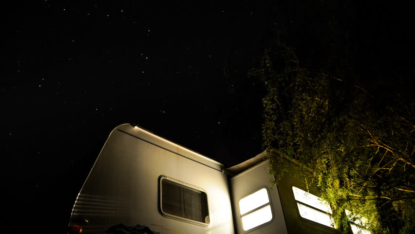 camper trailer sits under the stars as they go by and the lights go out