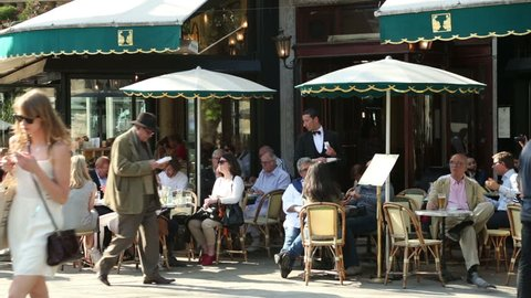PARIS - APRIL 26: Unidentified people sit at Paris cafe, Deux Magots on April 26, 2013 in Paris. Intellectuals and writers like Jean-Paul Sartre and Ernest Hemmingway were patrons of this famous cafe.