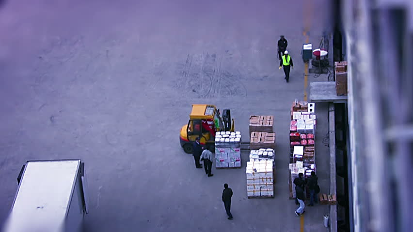 Early in the morning. Forklift loads food into a large cruise ship. Top view.