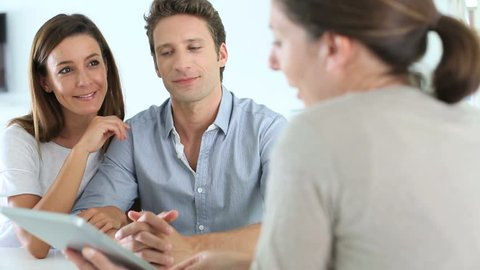 Couple meeting financial adviser in office