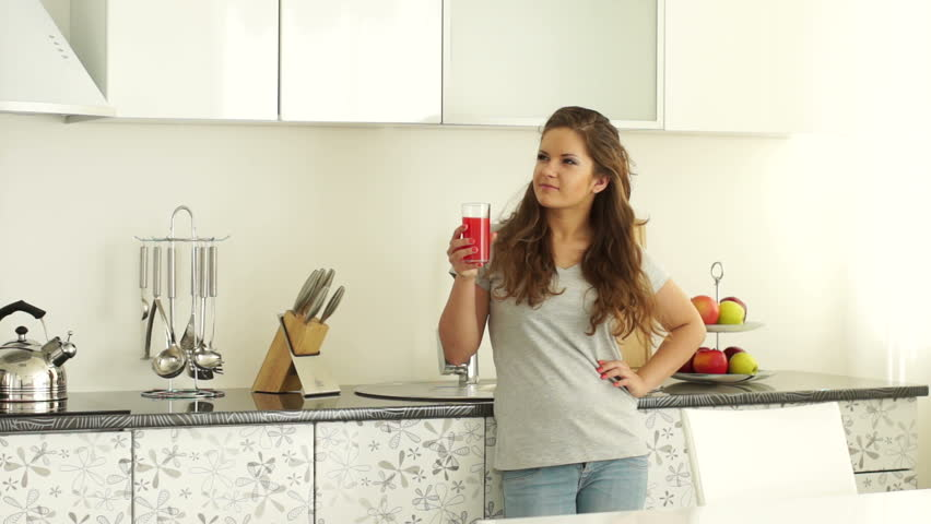 Girl Standing In The Kitchen With A Glass Of Juice. Lens Flare And ...