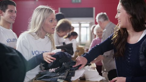 A beautiful young brunette woman makes a donation of clothing to a very grateful blonde haired voluntary worker.