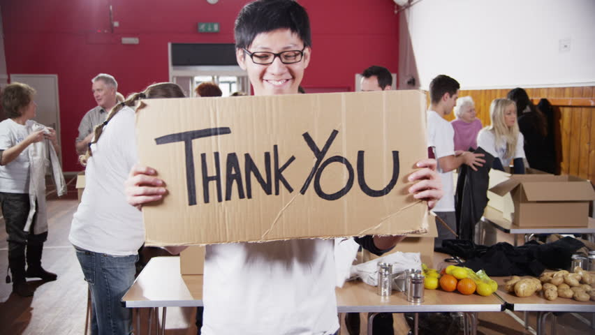 "A male charity volunteer of Asian ethnicity holds up a ""Thank You"" sign and smiles at the camera as his colleagues continue to work in the background. In slow motion."