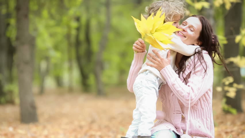 Happy child kissing her mother in autumn park