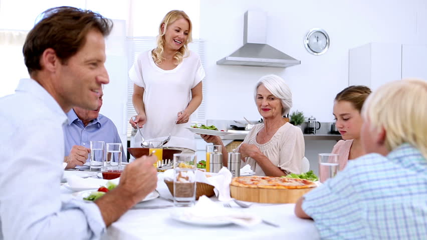 Woman serving salad at dinner to extended family at home in kitchen