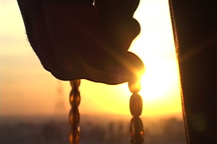 Silhouette of hand counting off prayer beads with bright orange setting sun in background in Mosul, Iraq. | Shutterstock HD Video #4064290