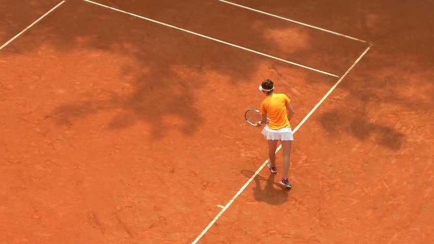 Girl play tennis outdoor on orange clay tennis court