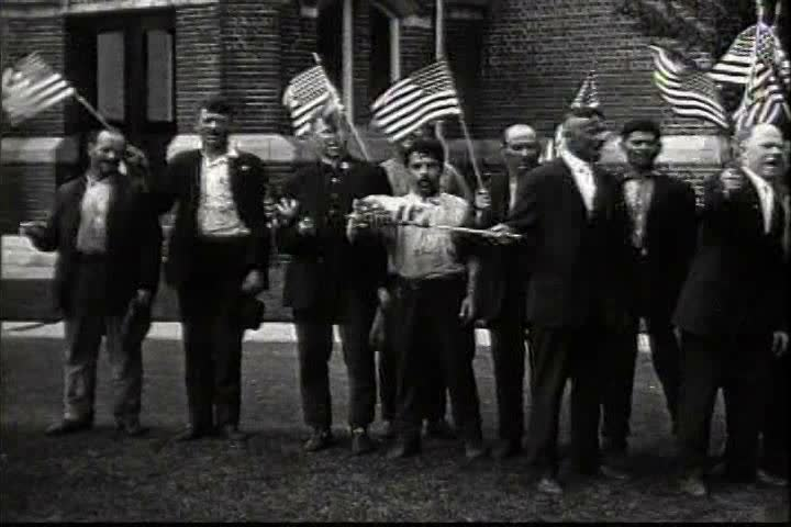 1910s - Patriotic immigrants wave the American flag in 1919.