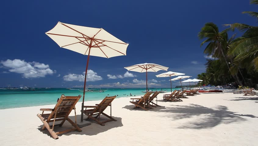 Sun umbrellas and chaise longues on caribbean beach with white sand