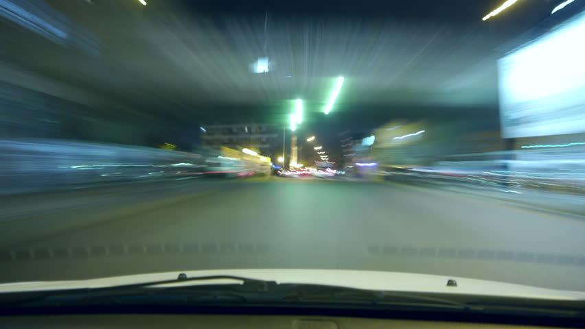 Driving a car time-lapse. POV - point of view. Night, Camera in the front, windshield reference. City, blurred motion, fast driving. HD.