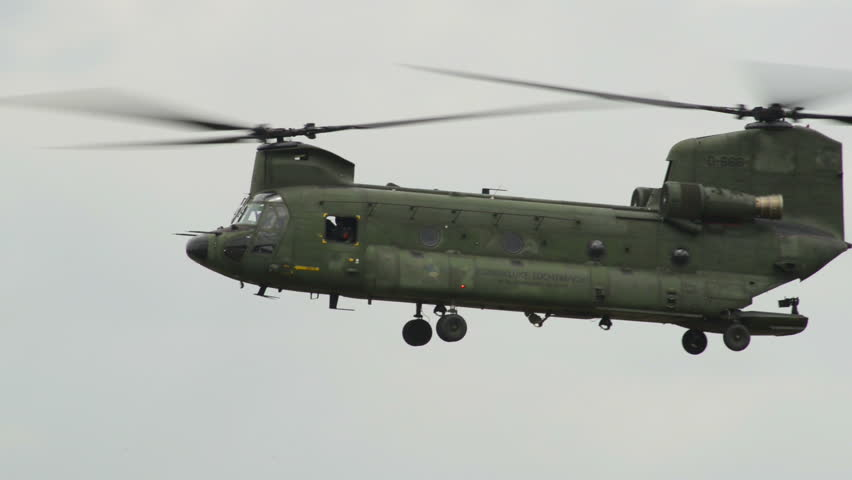 A Chinook CH-47 helicopter fly by with an Apache AH-64 in the background. 10958