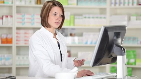 Smiling pharmacist chemist woman with prescription in pharmacy drugstore