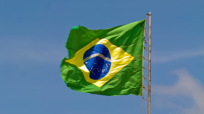 Brazilian flag flying in the wind against a blue sky
