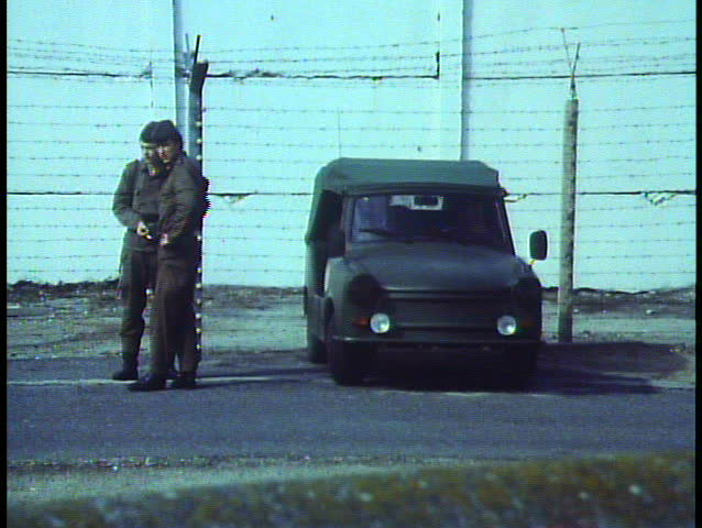 BERLIN - GERMANY - CIRCA - 1988: Berlin, Germany, The Berlin Wall in 1988, close up soldiers in DMZ, zoom out wide to artwork