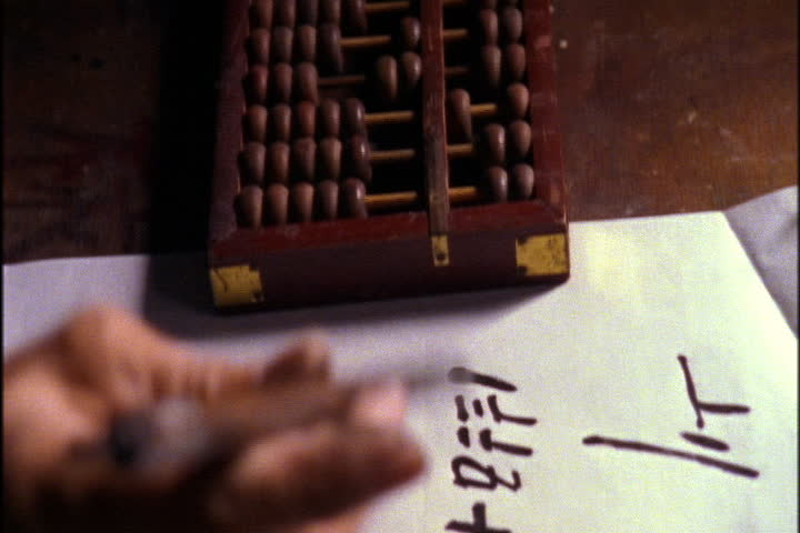SONG DYNASTY VILLAGE, CHINA - NOVEMBER 09, 1999: CU of hands counting beads on an abacus, then transcribing the numbers on white paper.