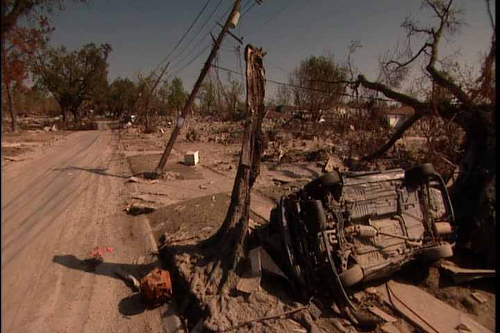 Police car drives past overturned car, tipping telephone poles and debris on road side  in New Orleans after Hurricane Katrina (October 2005)