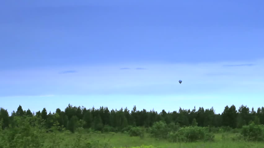 Hot air balloon landing in blue sky time-lapse