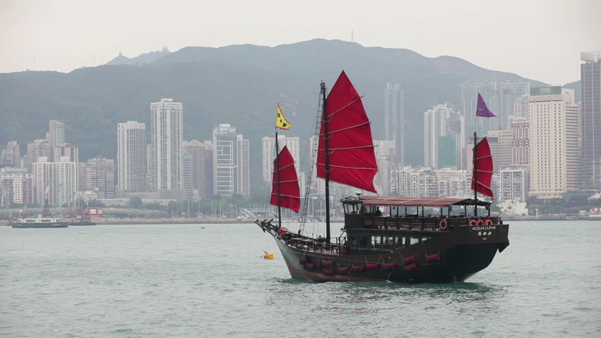 HONG KONG - MAY 7: Junk boat in Victoria Harbour in Hong Kong on May 7, 2013. The Junk boats with the characteristic red sails are one of the most iconic motives often photographed in Hong Kong.