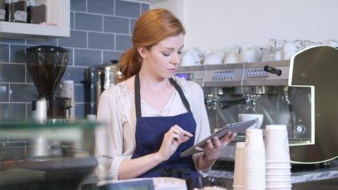 Barista using digital tablet in cafe