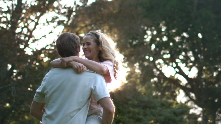 Young woman jumping in her husband's arms in slow motion