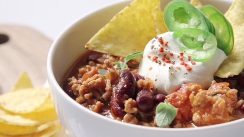 Chili con carne served with sour cream and tortilla chips