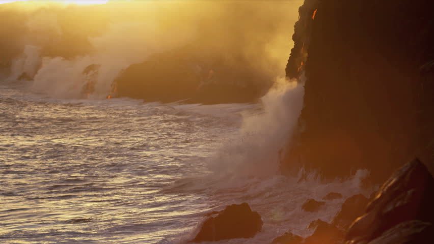 Steam from boiling lava flows beside jagged coastal rocks being cooled by crashing ocean waves at sunset Kilauea Big Island shot on RED EPIC