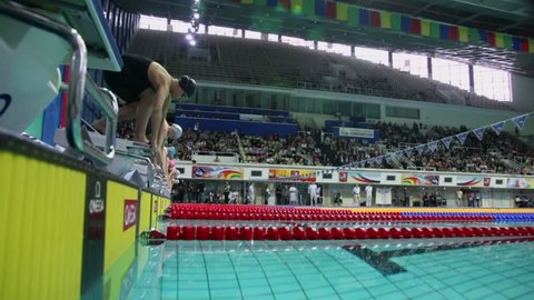MOSCOW - APR 20: Swimmers jump into water during start of swimming race in pool at Championship of Russia in Olympic Sports complex on April 20, 2012 in Moscow, Russia