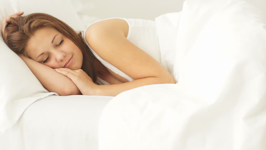 Young woman sleeping in bed waking up and smiling at camera