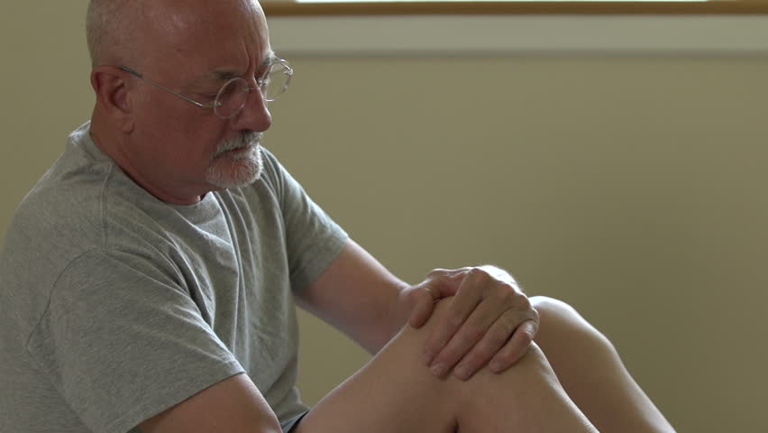 A senior main rubs his injured knee to sooth pain