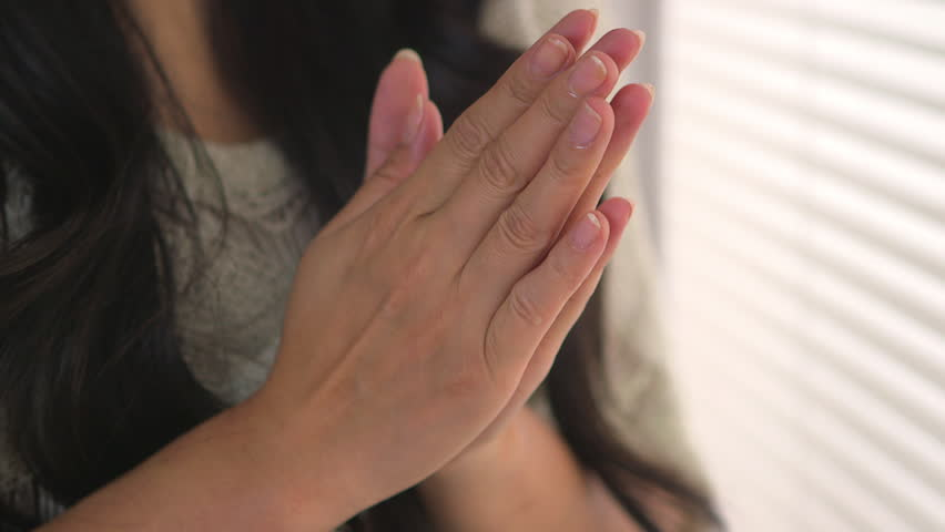 Worried Japanese woman holding her hands