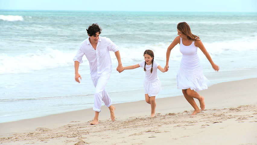 Loving Caucasian parents holding hands young daughter running together beach by ocean on vacation
