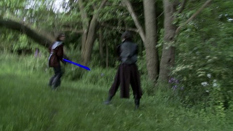 Two men duel with futuristic glowing blue laser swords.  Fighting on grassland in front of woods.  Hand held camera.  Long shutter speed gives strange movement and large light trails from the lasers.