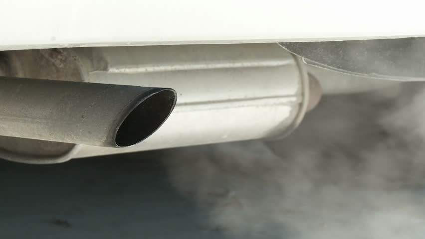 View of car exhaust pipe, emitting fumes, with details of car underside included.  Dolly in from right, at an angle to the car.