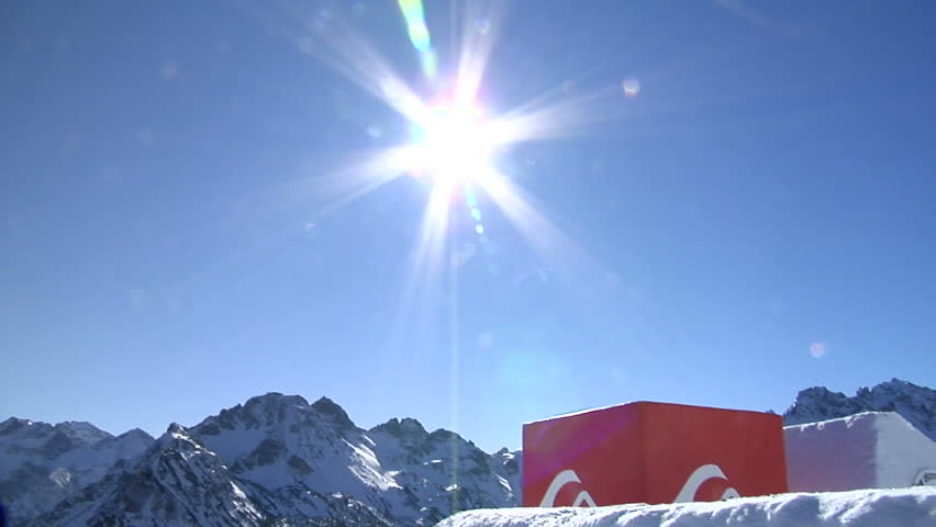 snowboarder jumps through sun in the blue sky