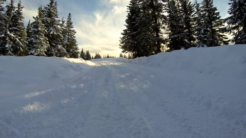 """Low angle driving POV around """"S"""" curve on snowy country road in Alaska."""