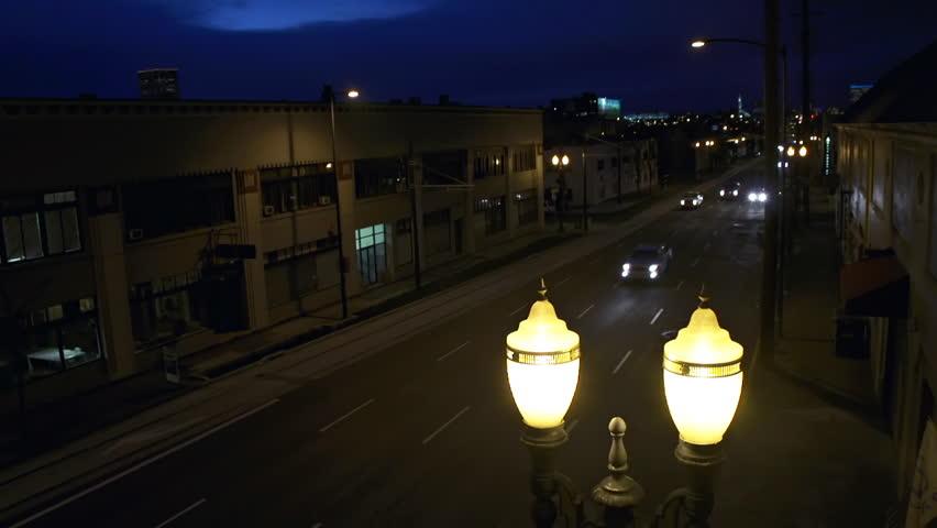 Traffic on dark streets of Portland, Oregon at night with Art Deco street lamp