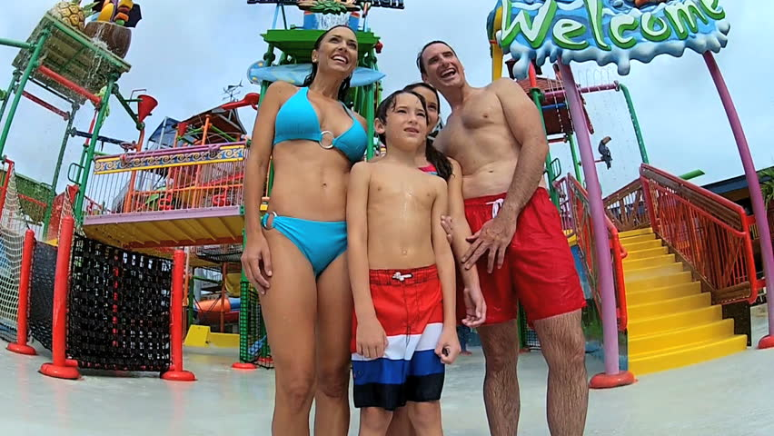 Laughing parents children having fun getting wet at water theme park