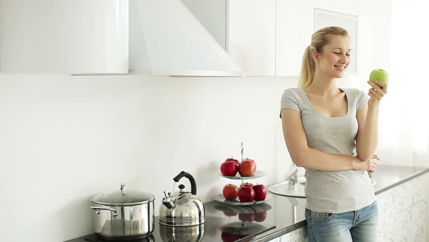 Cute Girl Standing In The Kitchen And Eating An Apple Stock ...
