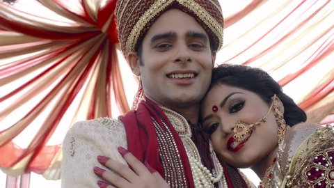 Shot of Indian bride and groom in traditional wedding dress posing under a mandap
