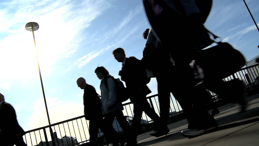 Silhouettes of city commuters in slow motion