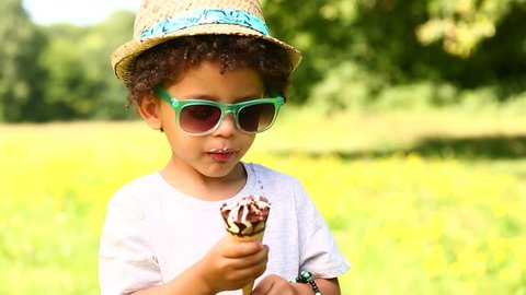 Little boy licking ice cream in a cone during summertime