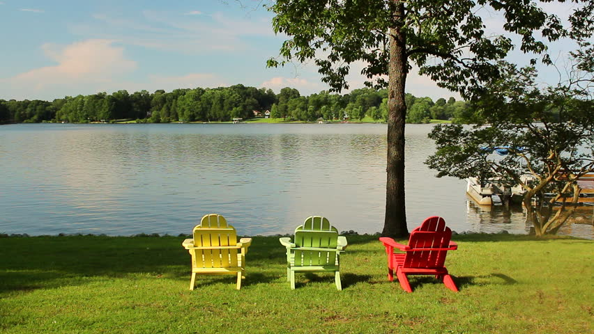 Three Colorful Adirondack Chairs Overlook A Sparkling Lake With A Boat In  The Distance   HD