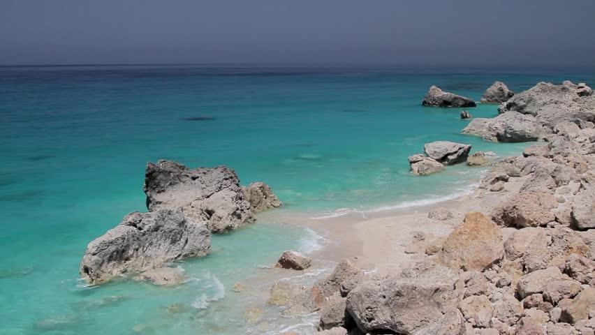 Rocky beach and azure blue waters of the Mediterranean sea. Island of Lefkada, Greece.